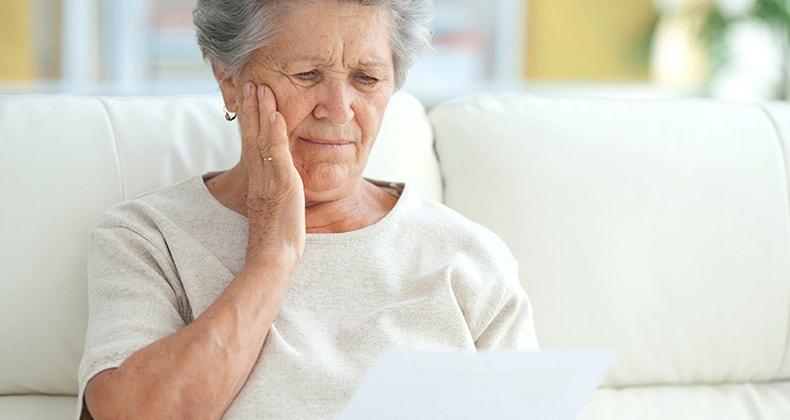 upset-elderly-woman-reading-letter-mst